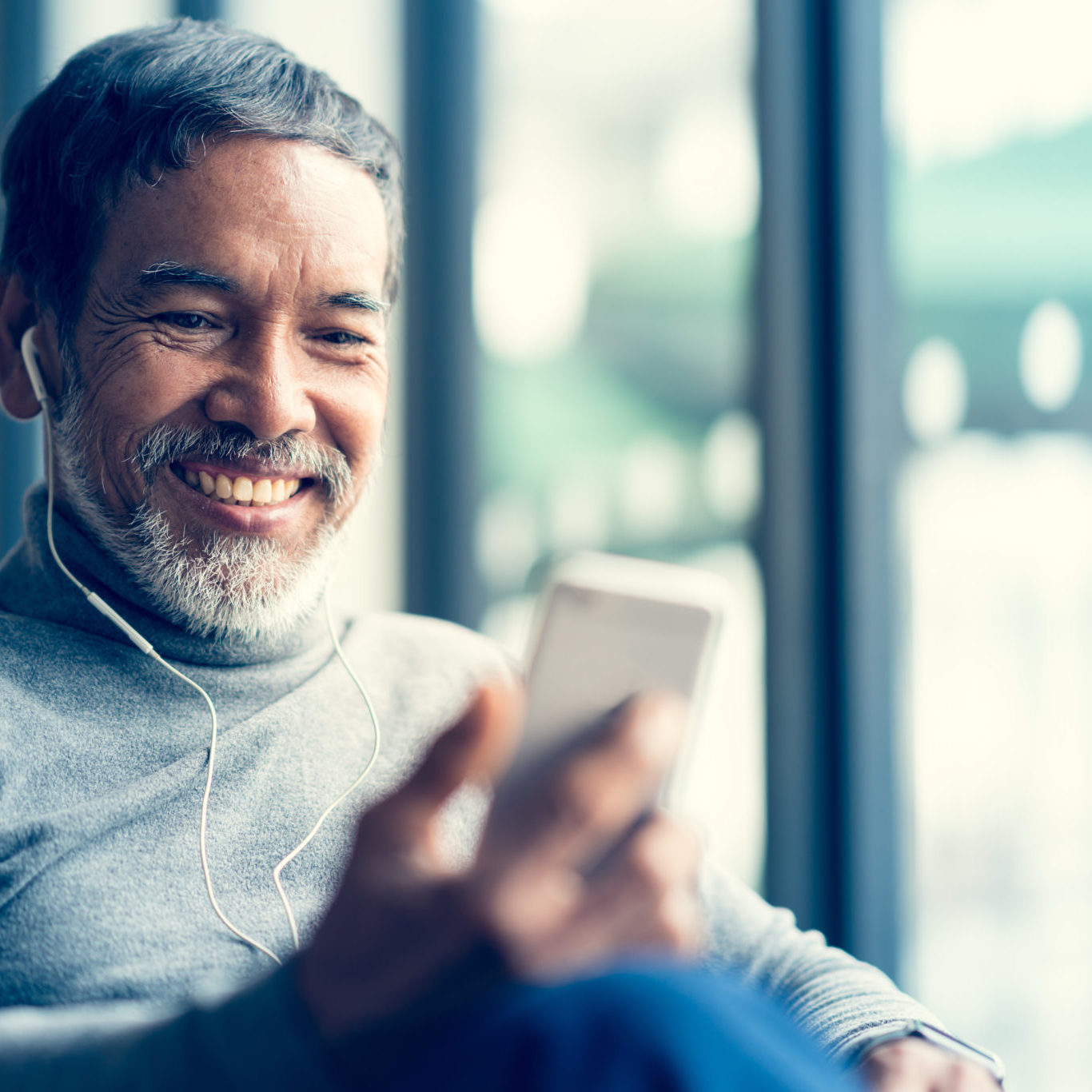 Portrait Smiling Attractive mature man retired with white stylish short beard using smartphone or listening music and sitting at coffee shop cafe. Serving internet via his gadget. Old man using social network internet technology